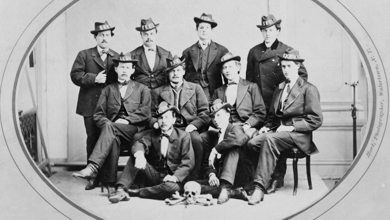 ten men of the Watertown Division 289 wearing hats with KKK in large letters, and with a skull and bones arranged on the floor in front of them. Watertown, N.Y. 1870s.